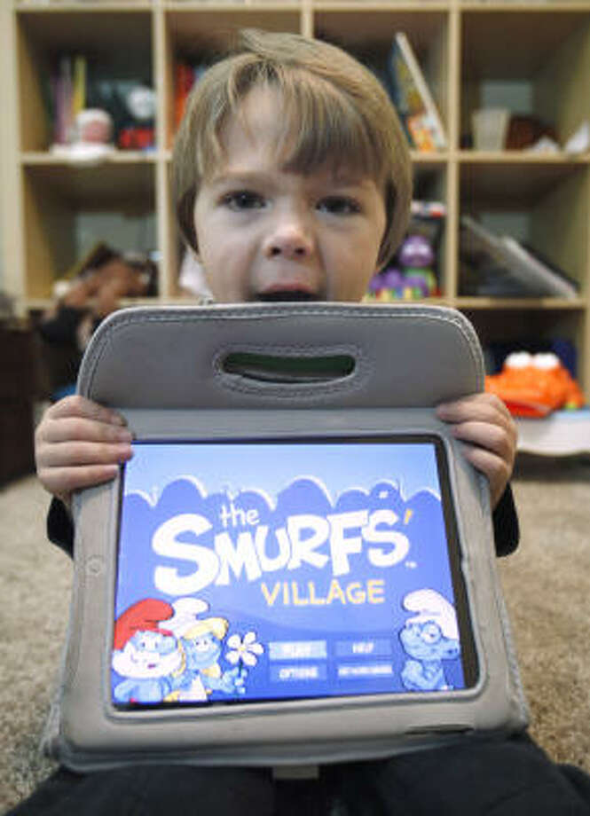 Sawyer Rummelhart, 4, holds his mother's iPad showing the game The Smurf's Village. Photo: Rich Pedroncelli, Associated Press