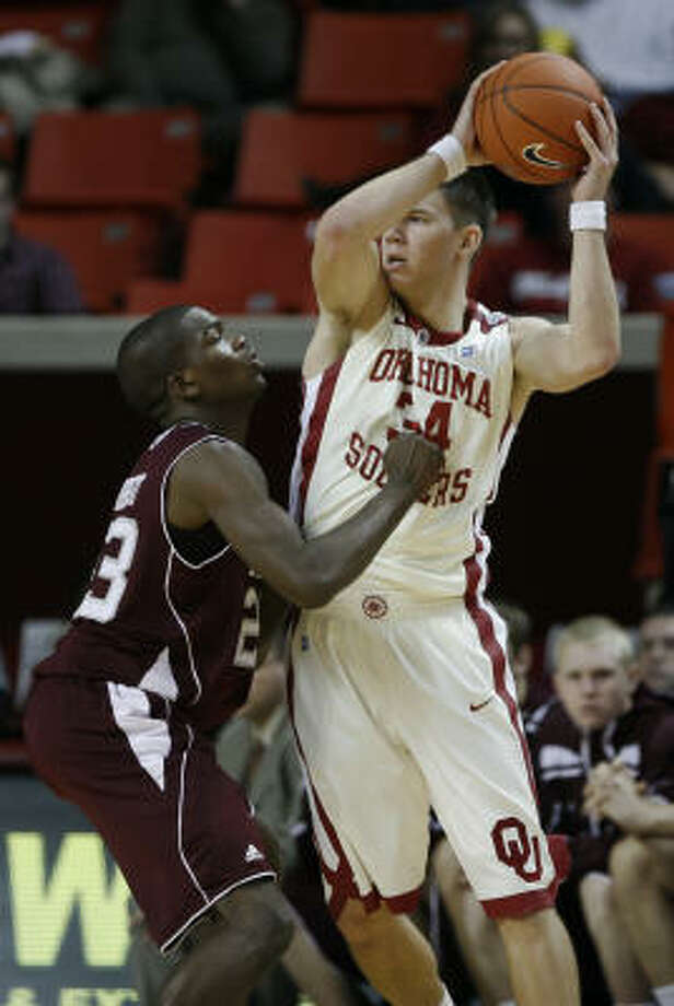 A&M guard Naji Hibbert, left, shows some of his improved defensive skills against Oklahoma's Cade Davis. Photo: Alonzo Adams, AP