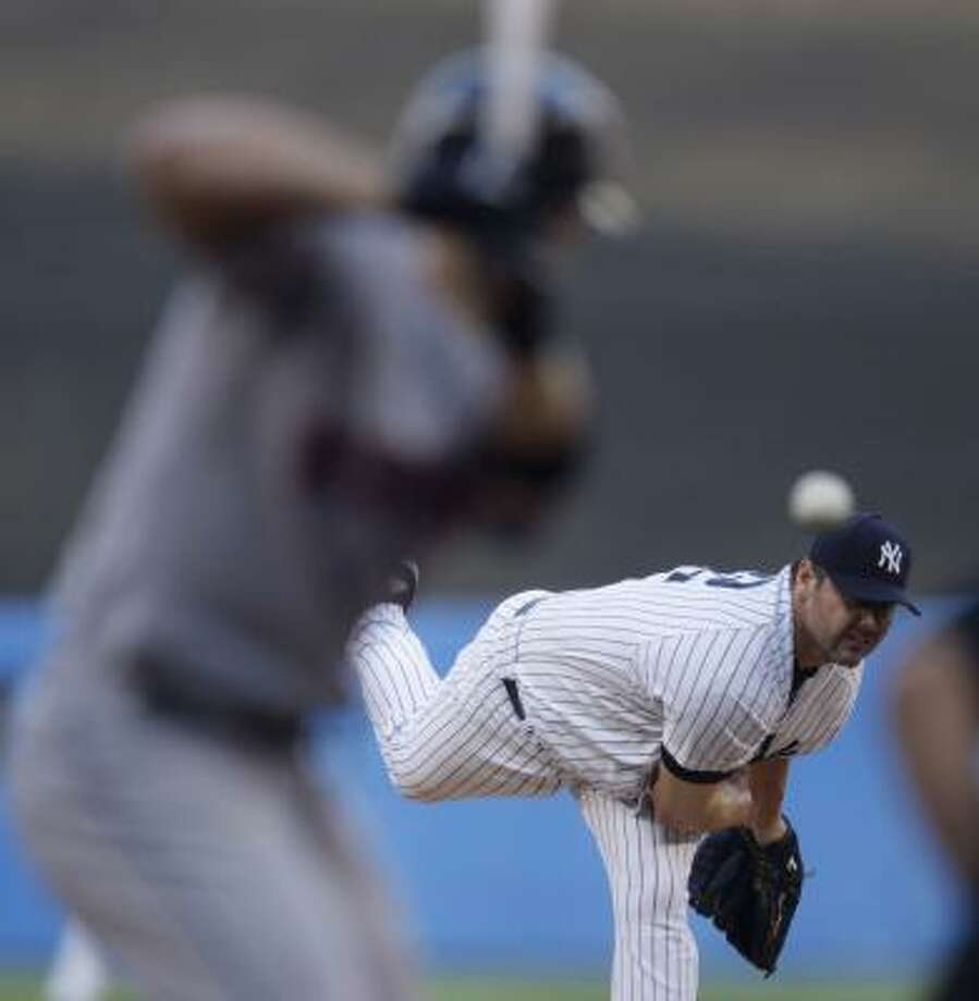 The Yankees' Roger Clemens delivers against the Mets' David Wright early in Friday's game at Yankee Stadium. Clemens struck out eight and allowed two runs, seven hits and one walk but took the loss. Photo: JULIE JACOBSON, ASSOCIATED PRESS