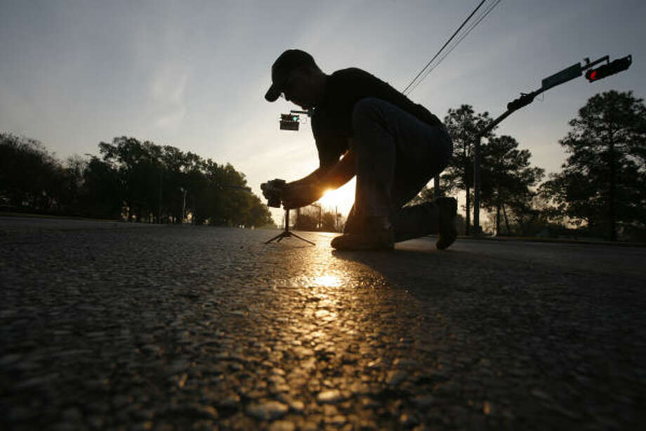 With his camera and tripod, Kim Enloe closes in on objects embedded into asphalt at the intersection of Market and Lockwood early on a recent Sunday. He always works at the same time of the morning to keep the effects of the natural light consistent. Photo: Steve Ueckert, Houston Chronicle