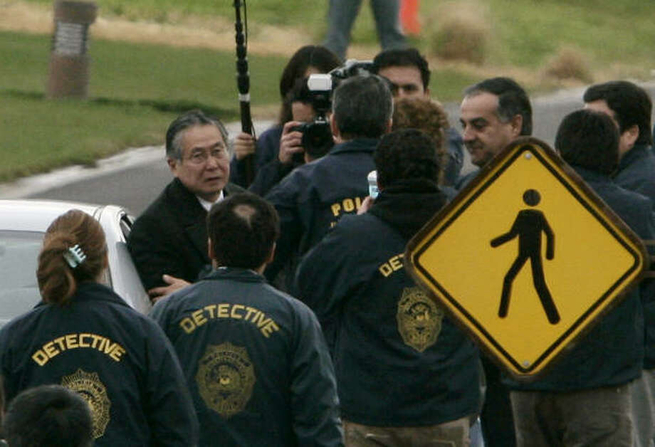 Chilean police officers surround Peru's former President Alberto Fujimori, left, as he leaves his house in Santiago, Chile, to be extradited to Peru. Photo: Claudio Santana, Associated Press
