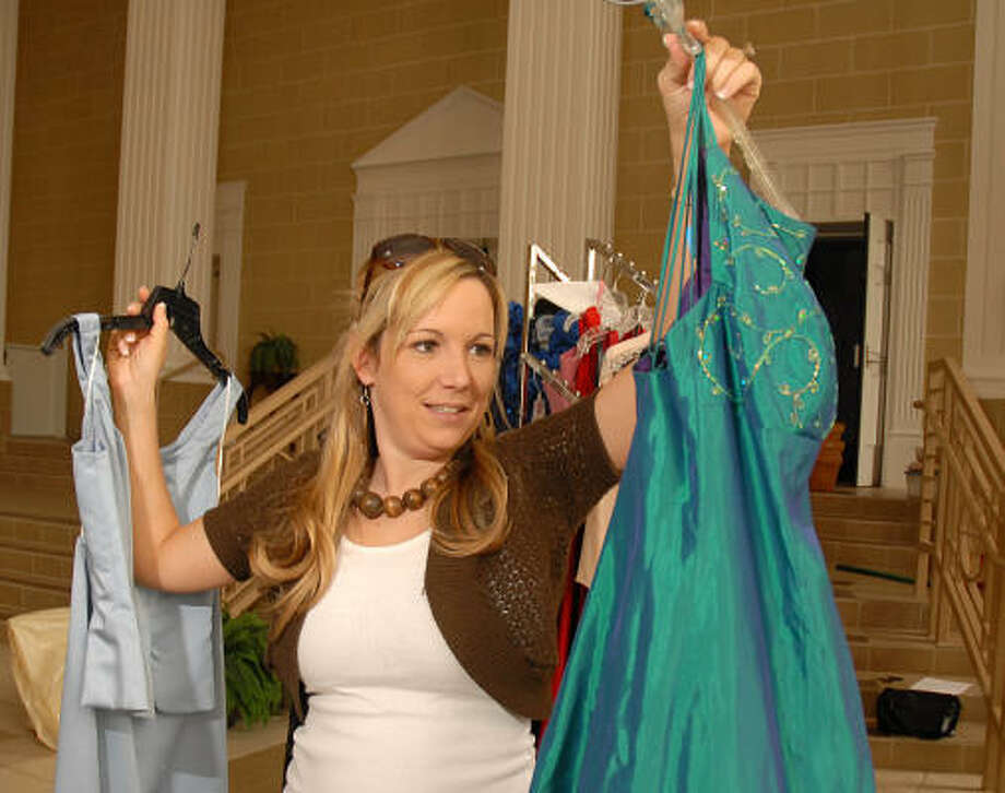 Conroe's First Baptist Church Under Construction Class for young, married women collected more than 200 prom dresses to give to area high school girls that can't afford to buy a dress. Here, Ashley Dupuis examines a donated dress. Photo: David Hopper, For The Chronicle