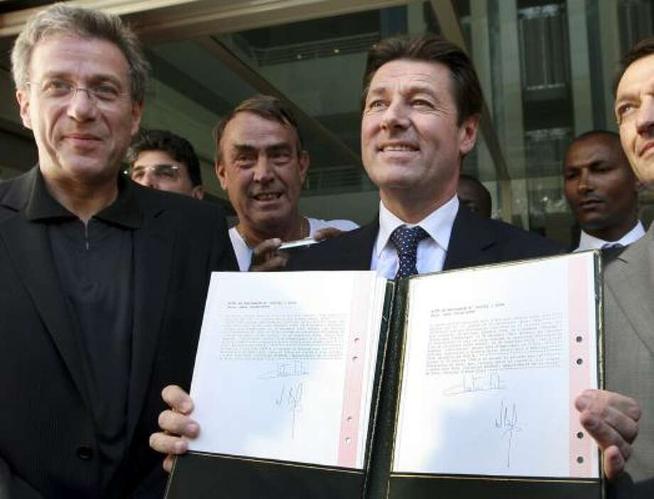 Christian Estrosi, the mayor of Nice, France, displays one twin's birth certificate with Angelina Jolie's obstetrician, Dr. Michel Sussmann, left, Sunday. Photo: CLAUDE PARIS, ASSOCIATED PRESS