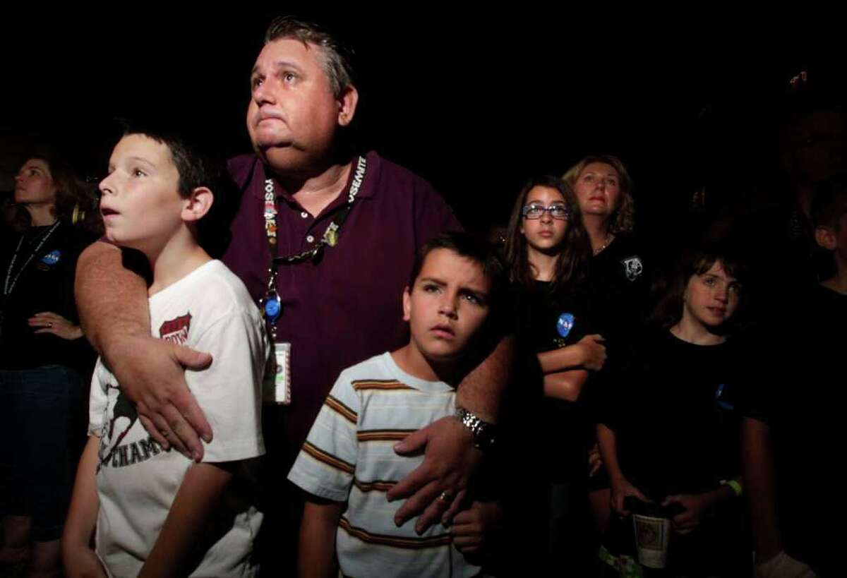 Spencer Cardenas, 9, (left) his brother, Trever, 7, and father, Steve, who has worked on the shuttle's backup flight systems for 23 years, look on as hundreds of Johnson Space Center employees and their families watched the space shuttle Atlantis land while projected on a large screen outside Building 1 at the Johnson Space Center during the shuttle's final mission ending the space shuttle program, Thursday, July 21, 2011. (Johnny Hanson / Chronicle) Steve Cardenas said watching the shuttle land for a final time was bitter sweet.