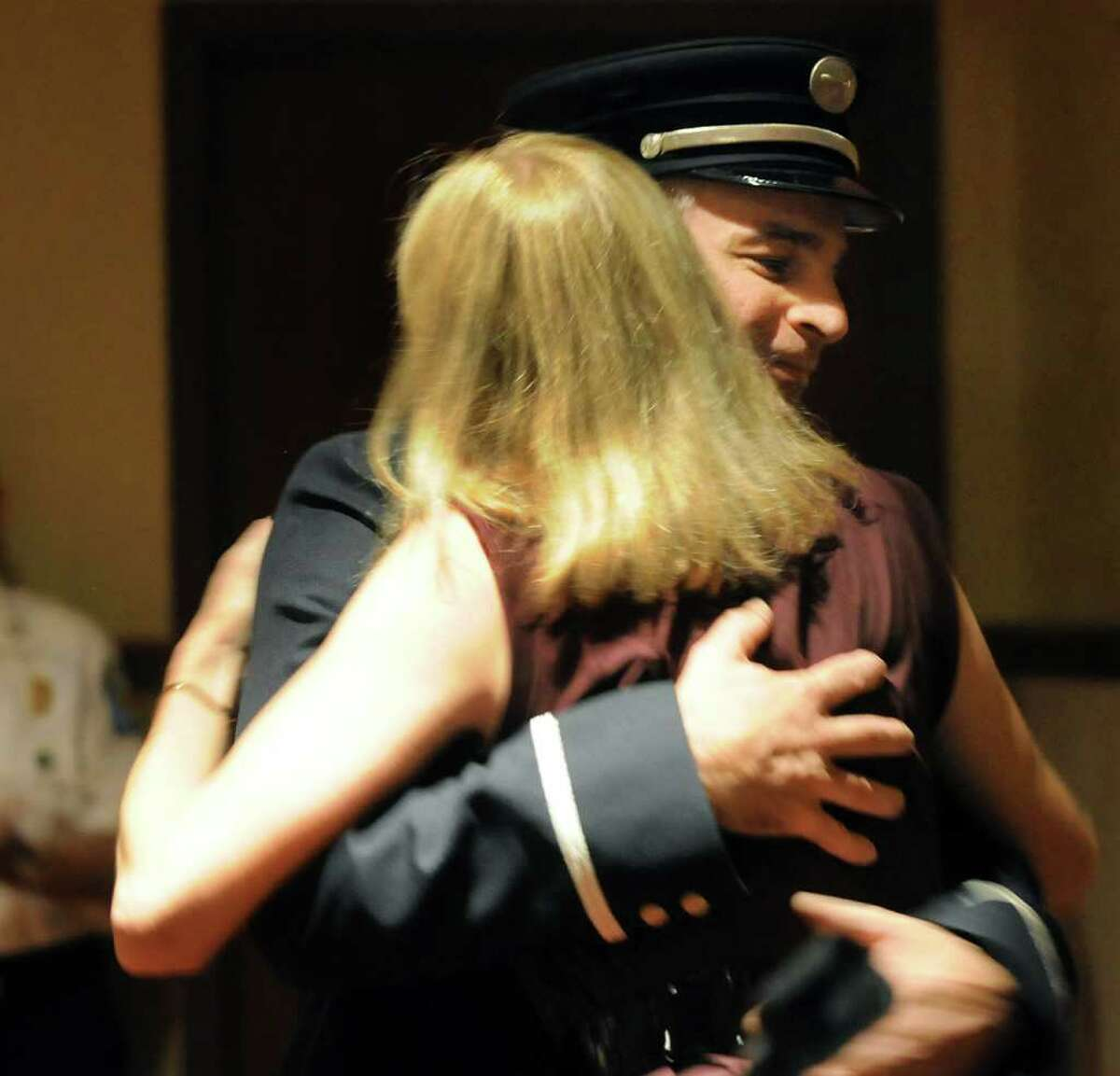 Newly promoted to captain, Paul Denio hugs his wife Melanie on Thursday, July 21, 2011, at the Hilton Garden Inn in Troy, N.Y. The Troy Fire Department promoted eight officers. (Cindy Schultz / Times Union)