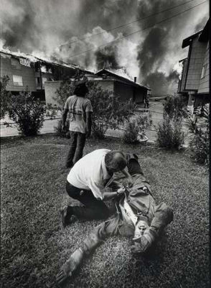 Damaged attic barriers played a part in the 1979 fire that destroyed 324 units of the Woodway Square apartments on Houston's west side. Here, a firefighter is treated for smoke inhalation. Photo: JOHN VAN BEEKUM, CHRONICLE FILE