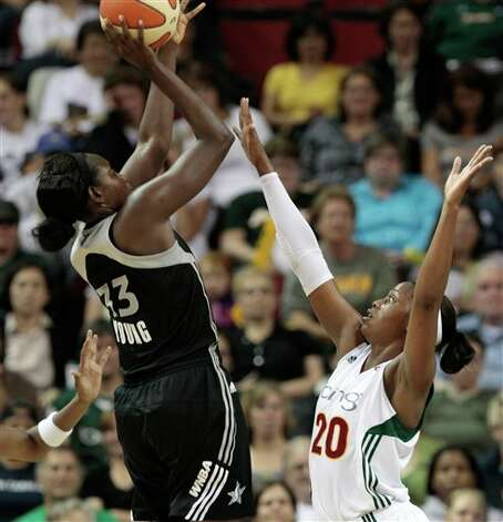 San Antonio Silver Stars' Sophia Young, left, shoots over Seattle Storm's Camille Little in the first half of a WNBA basketball game Thursday, July 21, 2011, in Seattle. (AP Photo/Elaine Thompson) Photo: Associated Press