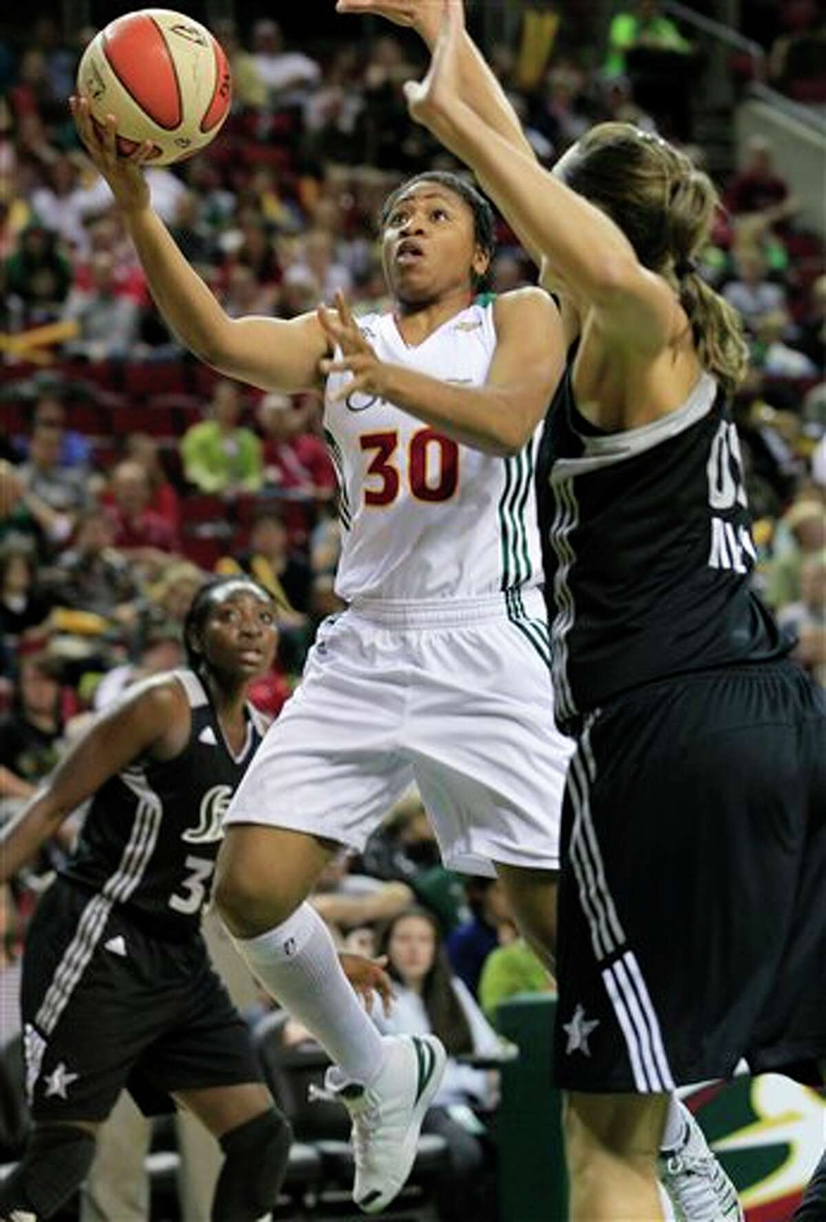 Seattle Storm's Tanisha Wright (30) drives as San Antonio Silver Stars' Sophia Young, left, and Ruth Riley defend in the first half of a WNBA basketball game Thursday, July 21, 2011, in Seattle. (AP Photo/Elaine Thompson)
