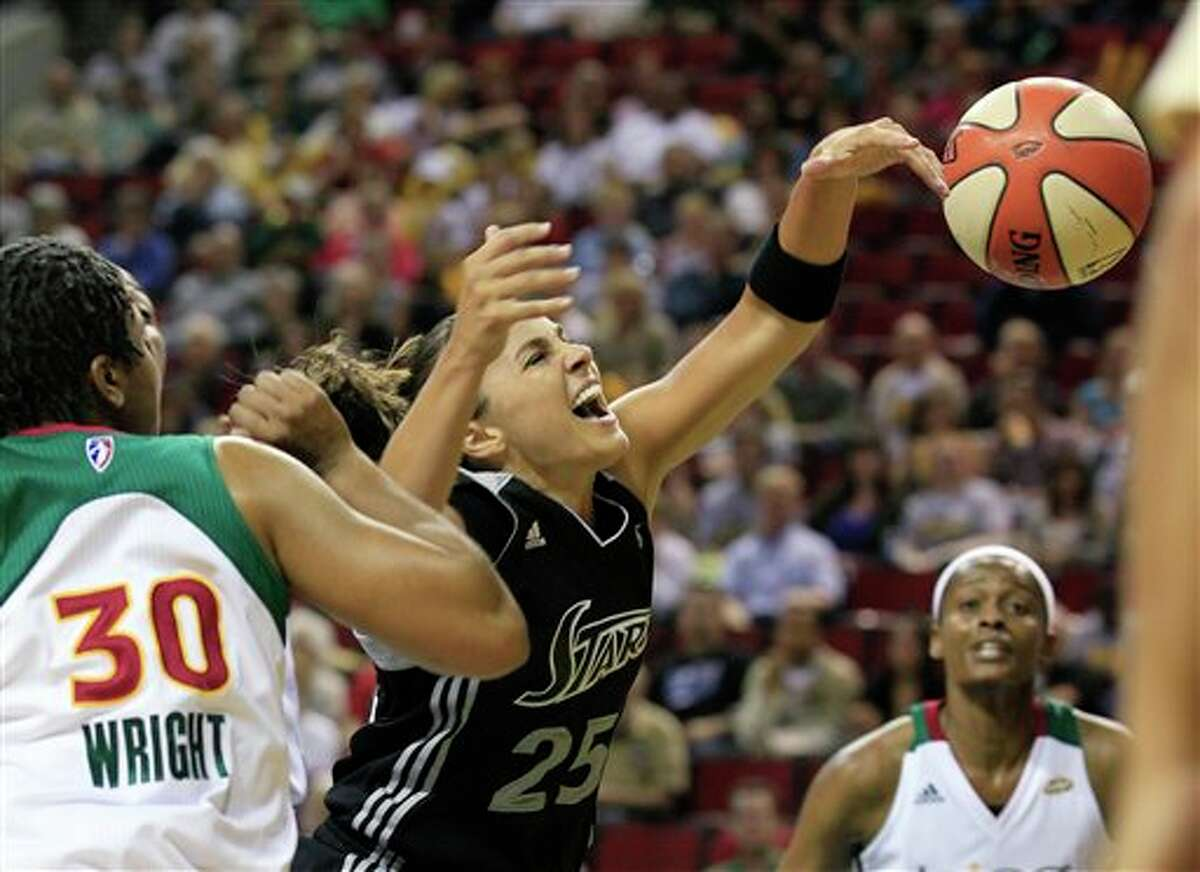 San Antonio Silver Stars' Becky Hammon (25) loses the ball as she drives the lane between Seattle Storm's Tanisha Wright (30) and Swin Cash in the first half of a WNBA basketball game Thursday, July 21, 2011, in Seattle. (AP Photo/Elaine Thompson)
