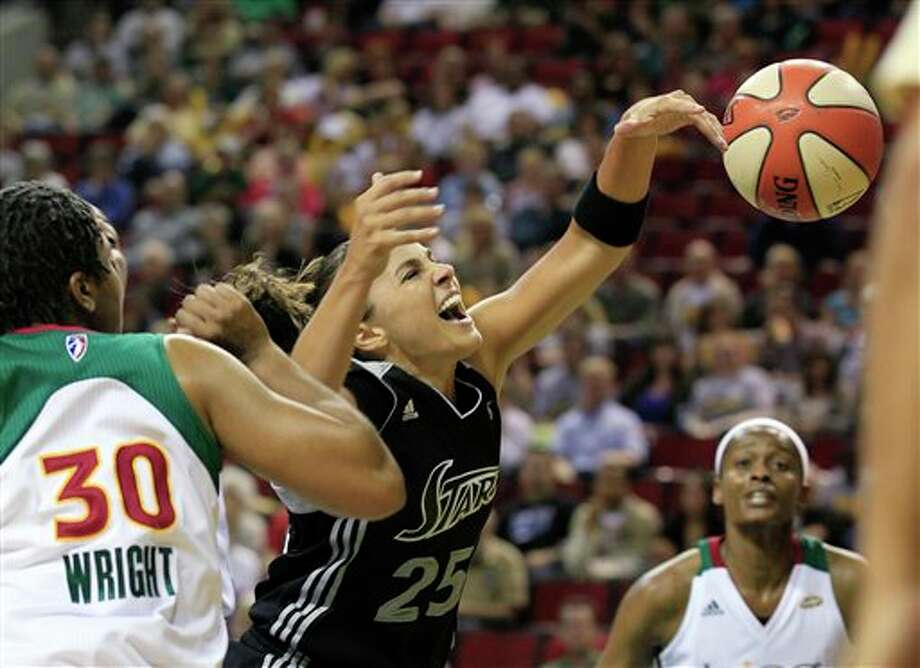 San Antonio Silver Stars' Becky Hammon (25) loses the ball as she drives the lane between Seattle Storm's Tanisha Wright (30) and Swin Cash in the first half of a WNBA basketball game Thursday, July 21, 2011, in Seattle. (AP Photo/Elaine Thompson) Photo: Associated Press