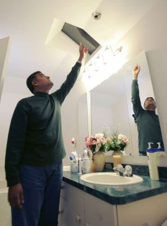 Srinivasan Nageswaran points to a hole in his bathroom ceiling in Freehold Township, N.J., where an iron meteorite came through the roof. Photo: Mike Derer, AP