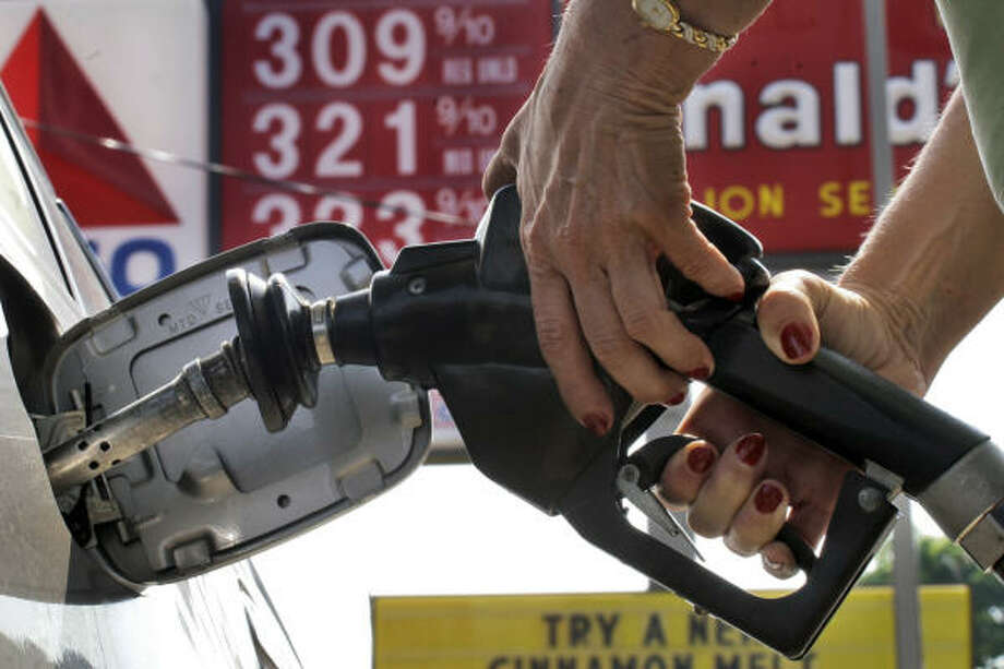 A woman pumps gas in Mt. Lebanon, Pa., Friday. Americans are expected to do slightly more driving this Memorial Day weekend than they did last year. But the near-record gas prices are prompting some travelers to take shorter trips and economize in other ways. Photo: GENE J. PUSKAR, AP