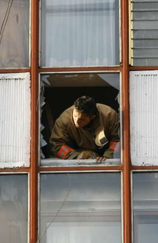 A firefighter peers out of a damaged building Friday after the device blew up. Photo: CLAUDIO CRUZ, AP