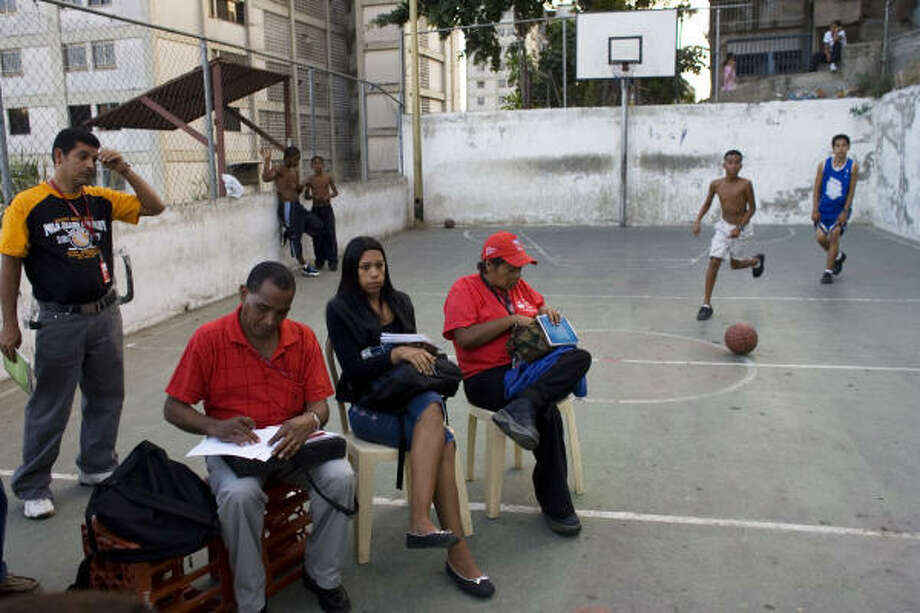 While boys play basketball in a Caracas slum, residents hold a community council meeting, where they discussed organizing a domino tournament and three-legged races for a street carnival. The meetings are designed to promote grass-roots democracy, but critics say the councils will allow Chavez to amass even more power by side-stepping locally elected officials. Photo: David Rochkind, For The Chronicle