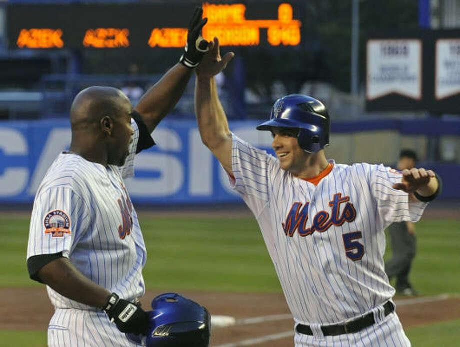 New York Mets' David Wright (5) greets Carlos Delgado as Delgado comes home after hitting a three-run home run in the first inning. Photo: Bill Kostroun, AP