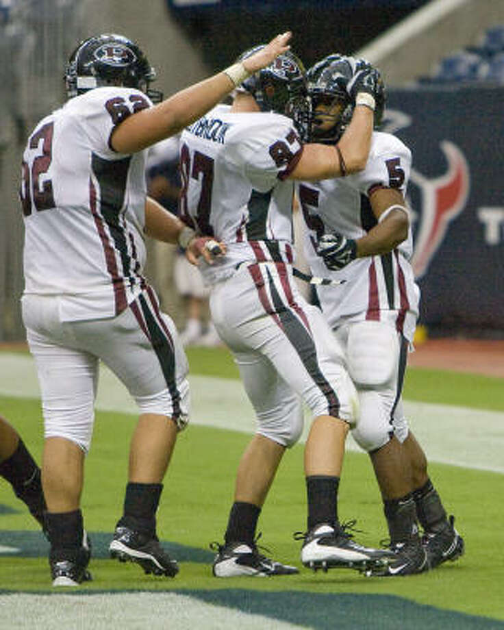 Pearland's Kasey Carrier (No. 5, right) is congratulated by teammates Alexander Freas (No. 62) and Landon Westbrook (No. 87) after Carrier scored a touchdown in the second half as Pearland played Madison on the opening weekend of high school football at Reliant Stadium. Photo: Steve Campbell, Houston Chronicle