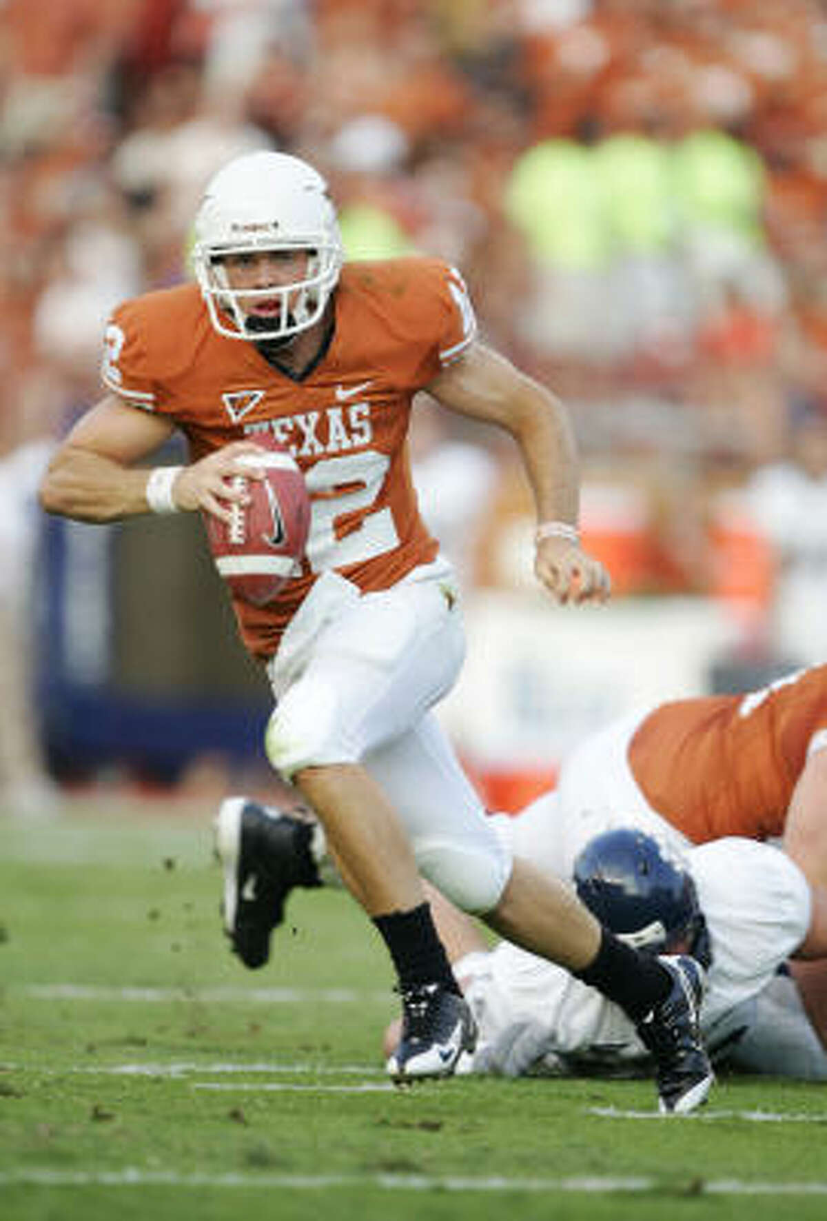 Under pressure, quarterback Texas quarterback Colt McCoy breaks out of the pocket to run for a touchdown against the Rice Owls in the first quarter on Saturday at Darrell K Royal-Texas Memorial Stadium in Austin.