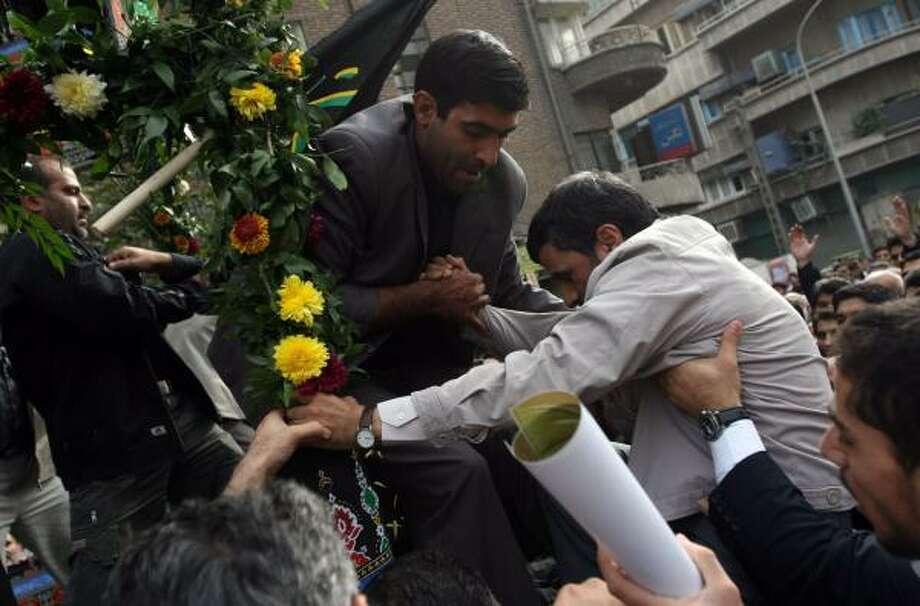 A bodyguard helps Iranian President Mahmoud Ahmadinejad, right, climb onto a truck during a religious ceremony Saturday in Tehran. Photo: HASAN SARBAKHSHIAN, ASSOCIATED PRESS