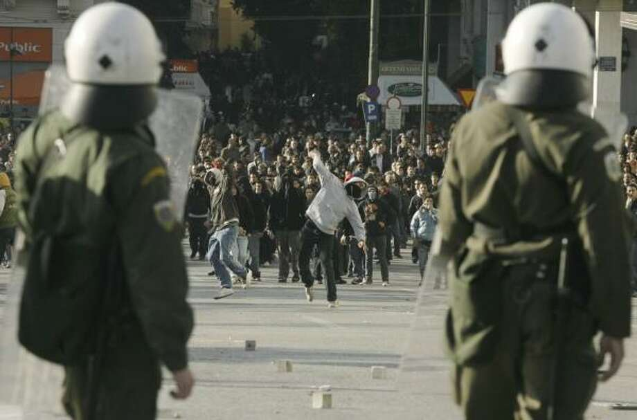 Protesters throw stones at riot police Tuesday in Athens. The Greek government is already facing a troubled economy, poor job prospects for students and financial scandals. See more photos on chron.com. Photo: PETROS GIANNAKOURIS, ASSOCIATED PRESS