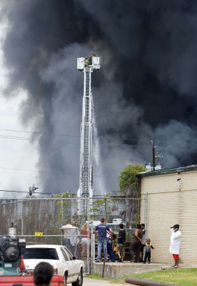 A crowd watches Houston firefighters battle the blaze at a building at Old Clinton Road and Shotwell on Saturday. Photo: James Nielsen, Chronicle