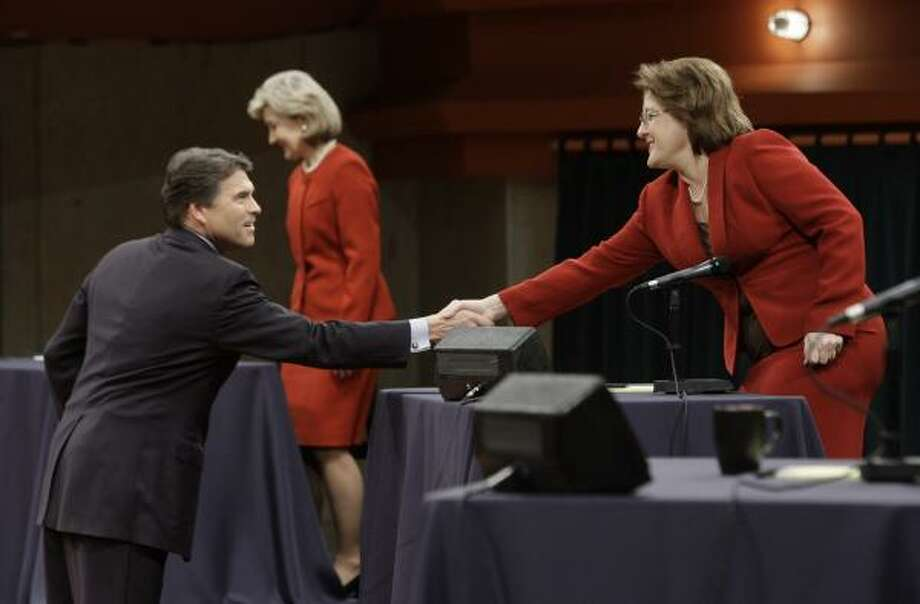 Before the fireworks, Debra Medina, right, greets Gov. Rick Perry as Kay Bailey Hutchison prepares to take her seat before the GOP gubernatorial debate at the University of North Texas in Denton on Thursday. Photo: LM Otero, Associated Press