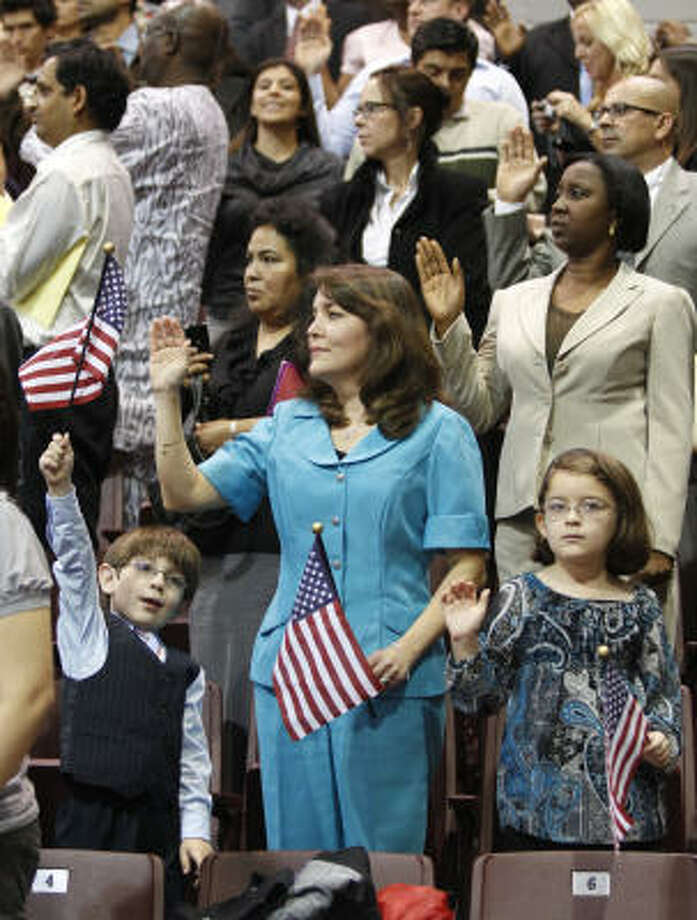 David Rodriguez, 5, and his sister, Daniela Rodriguez, 6, listen as mom Lina Orozco takes the oath of citizenship. Photo: Melissa Phillip, Chronicle