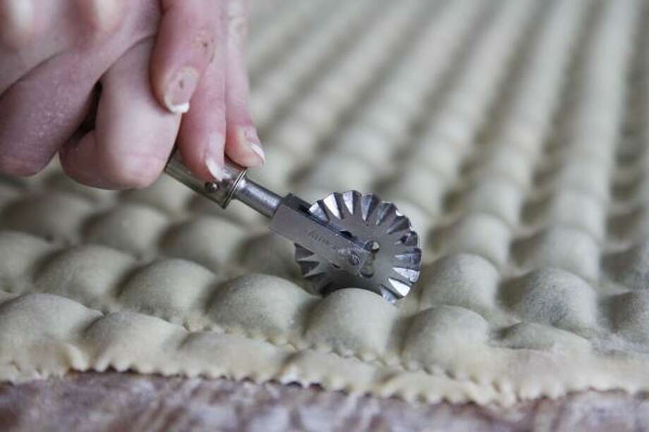 Sara Ballard cuts freshly filled ravioli. Photo: MIKE KEPKA PHOTOS :, STAFF