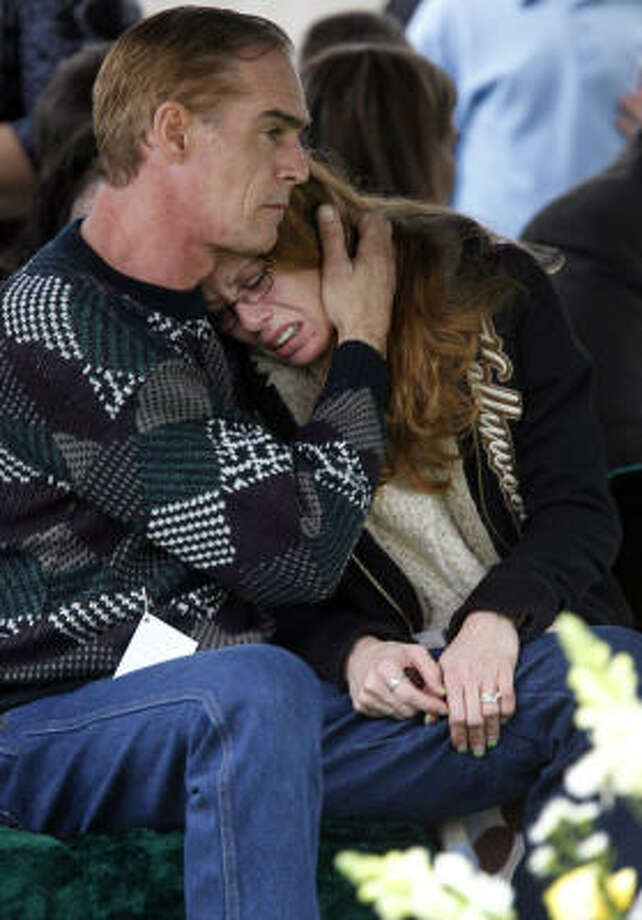 David Davis comforts his wife, Angela Davis, during service for her son,  Jonathan Foster, 12, at South Park Cemetery Tuesday, Jan. 4, 2011, in Pearland.  He was abducted and killed on Christmas Eve and his burned body was found in a drainage ditch on Dec. 28. Mona Yvette Nelson, 44, has been charged with capital  murder in Jonathan's death.  ( Melissa Phillip / Houston Chronicle ) Photo: Melissa Phillip, Houston Chronicle
