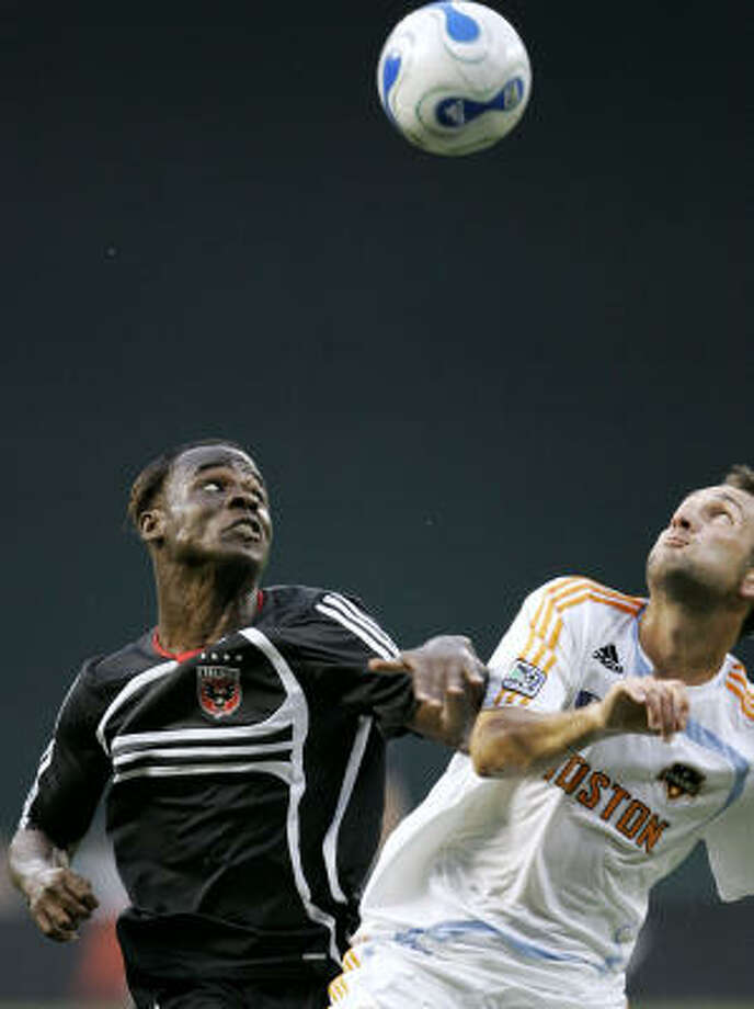 United's Guy-Roland Kpene, left, and the Dynamo's Ryan Cochrane fight for possession in the first half. The Dynamo defense gave up two goals for the first time this season in Saturday's 2-1 loss at Washington. Photo: Haraz N. Ghanbari, AP