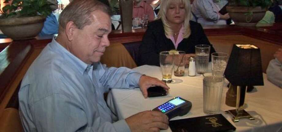 Wayne Smith, a diner at Ray's Killer Creek restaurant in Alpharetta, Ga., swipes his credit card at his table. Sit-down restaurants are the last bastion of resistance to card swiping. Photo: JASON BRONIS, ASSOCIATED PRESS