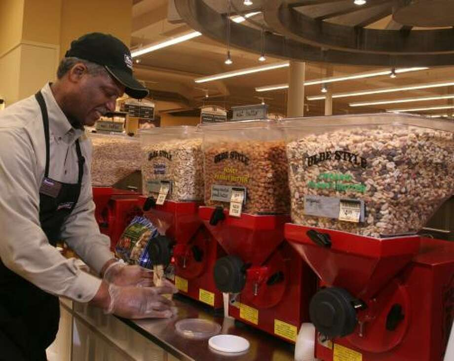"Talmadge Jackson, a nut kiosk specialist at Randalls on Westheimer near Shepherd, grinds unsalted cashew nut butter. The store has undergone a major renovation called a ""lifestyle"" remodel. Photo: GARY FOUNTAIN, FOR THE CHRONICLE"