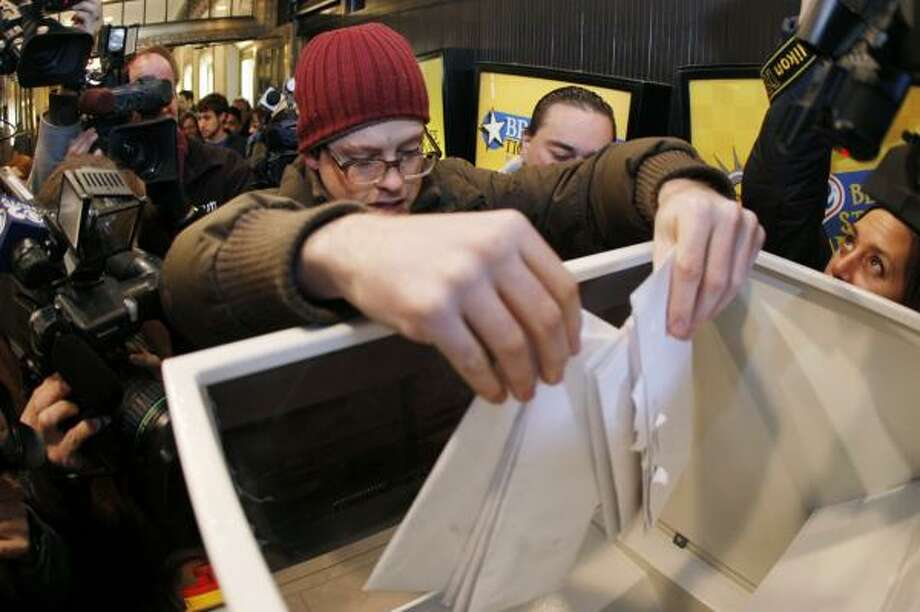 Jose Soegaard of Brooklyn drops his unwanted personal documents into a giant paper shredder in Times Square on Friday. Photo: JULIE JACOBSON, ASSOCIATED PRESS