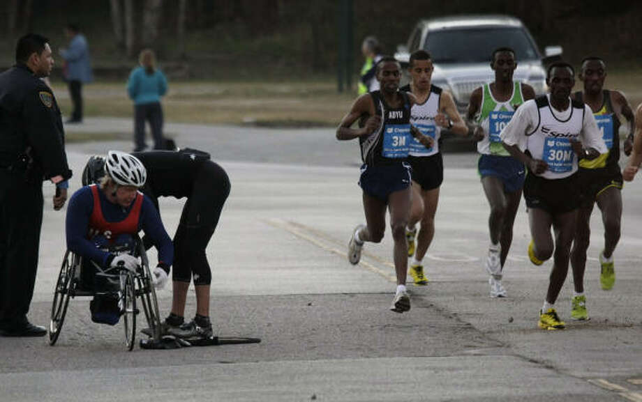 Wheelchair athlete Kevin Saunders of Houston gets some help with a flat tire as the lead group of runners passes him on White Oak Drive during the Chevron Houston Marathon. Photo: Smiley N. Pool, Chronicle