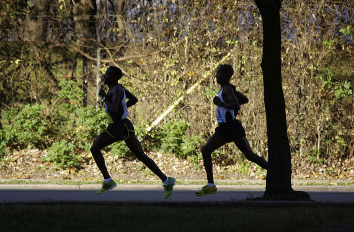 David Cheruiyot, of Kenya, right, trails Kasime Adilo of Ethiopia as they prepare to make the turn onto Allen Parkway during the Chevron Houston Marathon.