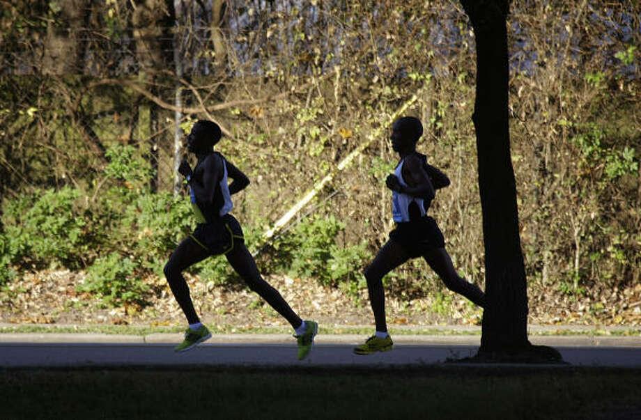 David Cheruiyot, of Kenya, right, trails Kasime Adilo of Ethiopia as they prepare to make the turn onto Allen Parkway during the Chevron Houston Marathon. Photo: Smiley N. Pool, Chronicle