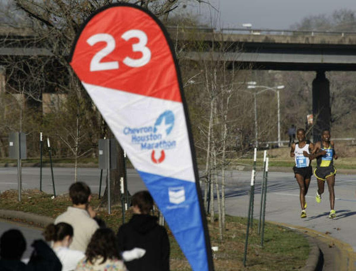 David Cheruiyot, of Kenya, left, runs stride-for-stride with Kasime Adilo of Ethiopia as they near the 23-mile marker on Allen Parkway during Chevron Houston Marathon.