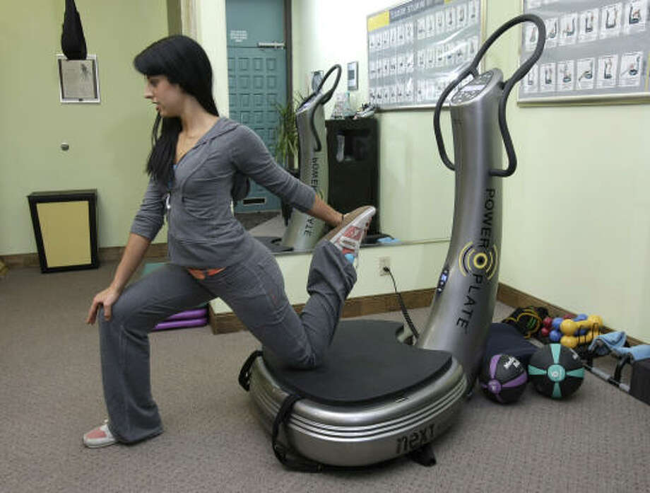 Methode Fitness trainer Samantha Pope demonstrates a stretch while using the Power Plate machine. Photo: Brett Coomer, Chronicle