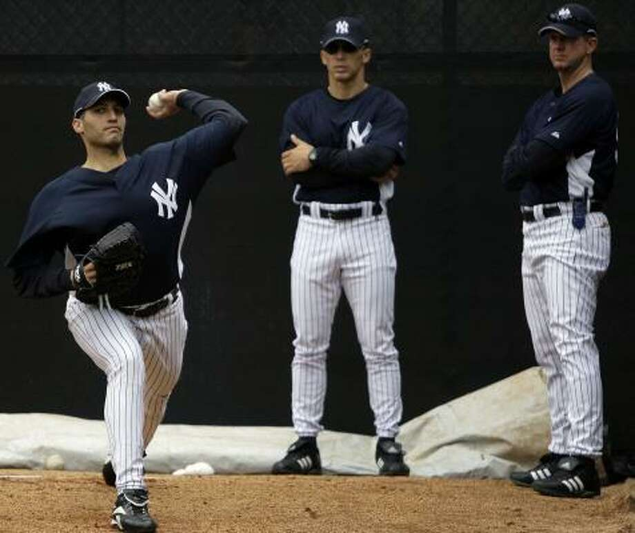 Yankees manager Joe Girardi, center, and pitching coach Dave Eiland watch as Andy Pettitte works out during spring training. Photo: JULIE JACOBSON, AGENCY