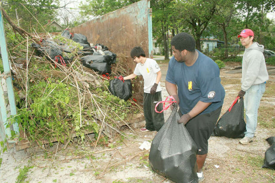 EAST END CLEAN SWEEP: Oliver Velazquez, Alusine Bangura, and Sion Aguilar throw trash collected into the bin near Eastwood Park during East End Clean Up Day. Photo: Pin Lim, For The Chronicle