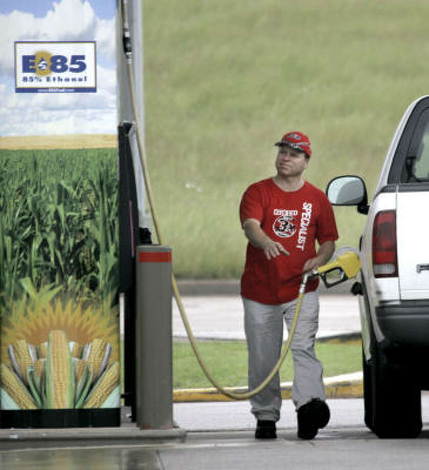 A sign on the pump advertises the ethanol content of the gasoline as a motorist reaches for the gas pump in his truck at a filling station in Bellmead, Texas, on May 6. Photo: LM Otero, AP