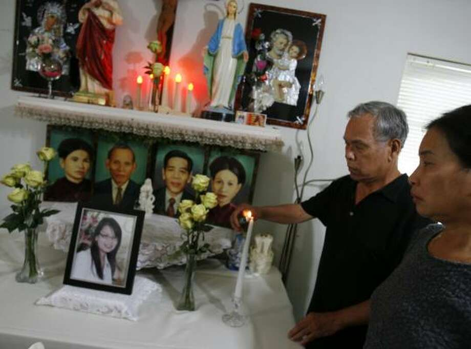 Thuong Trung Vu, left, and Hoi Thi Pham, parents of Thuy Thu Pham Vu, pause at a shrine they prepared in their Houston home for the 27-year-old who died in the bus crash near Sherman. Photo: SHARÓN STEINMANN, CHRONICLE