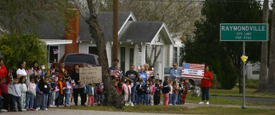 Staff and students from Otis Klar Head Start line up as Staff Sgt. Hector Leija's funeral procession approaces Monday. Photo: Nick De La Torre, Chronicle