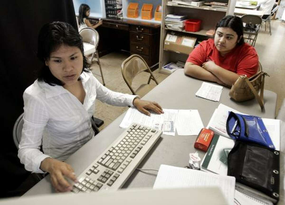 Martha Pantoja, a volunteer with the Nashville Wealth Building Coalition, helps Iris Castillo Ortiz prepare her income taxes at a community center in Nashville, Tenn.