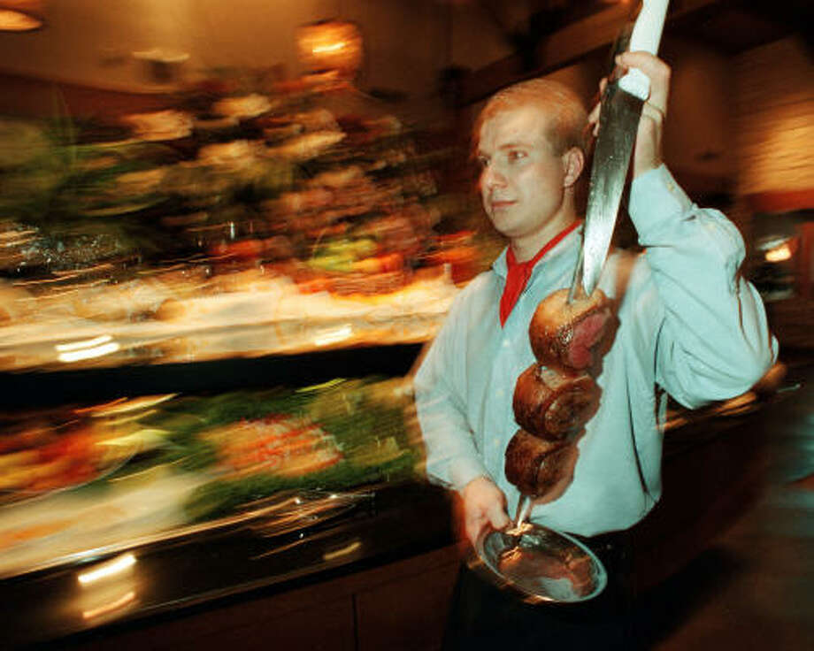 Gaucho Jarbas Gottardo carries a skewer of meat while serving guests at Fogo de Chao. Photo: Dave Rossman, Special To The Chronicle