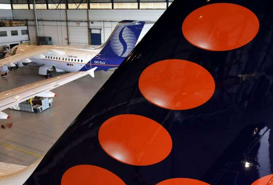 The tail of an Airbus 319 sports the Brussels Airlines logo after its repainting to add a 14th dot, while a jet with the design of the old SN Brussels airline awaits its new paint job. Superstition over the number 13 prompted the redesign for the airline, the successor to SN Brussels and Virgin Express. Photo: YVES LOGGHE, ASSOCIATED PRESS