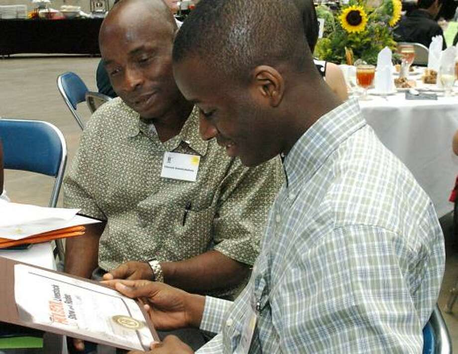 Dulles High School grad Chibueze Amanchukwu, right, and his father, Vincent, look over a $15,000 rodeo scholarship certificate. Photo: KIRK SIDES, FOR THE CHRONICLE