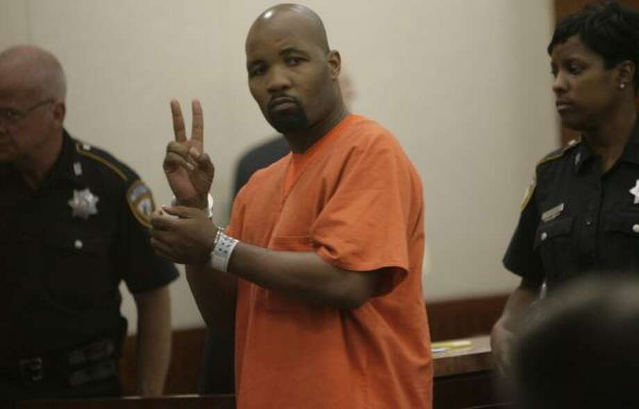 Former world champion boxer Reggie Johnson flashes a 'peace' sign to his sister Angela Johnson as he leaves a courtroom after hearing the charge against him and requesting a bail reduction. Photo: JULIO CORTEZ, CHRONICLE