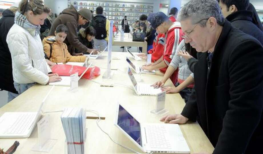 Customers look over Apple computers at a store in New York on Christmas Eve. A report that federal prosecutors are investigating whether former Apple officials forged documents to maximize profit from stock options did not ultimately have a negative effect on the stock price of the maker of iPods. Photo: Stephen Chernin, Getty Images