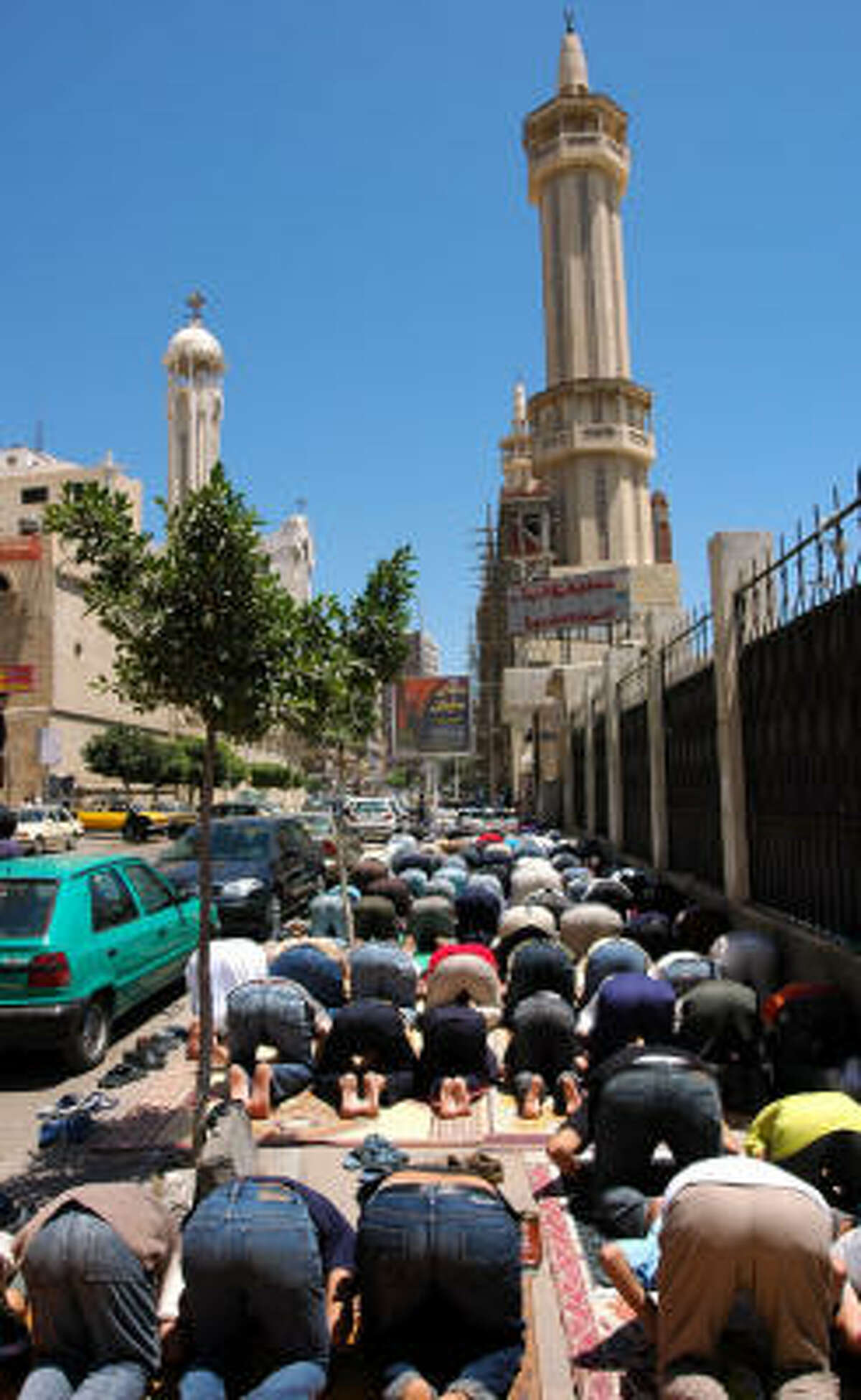 Muslims pray outside a Mosque that is next to a church where a Muslim was accused of killing Christians.