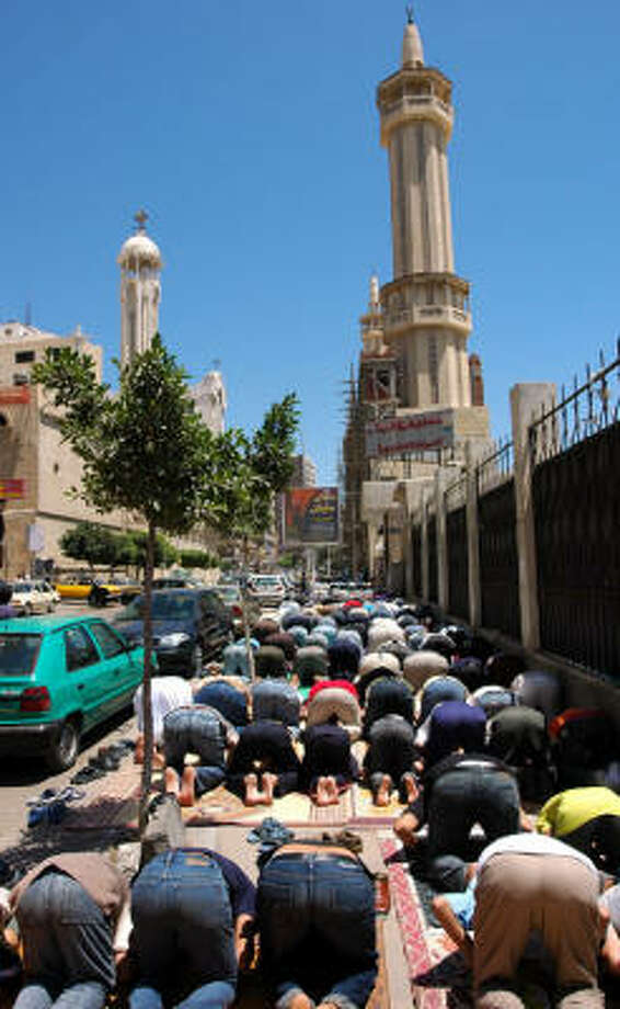 Muslims pray outside a Mosque that is next to a church where a Muslim was accused of killing Christians. Photo: Mohamed El-Dakhakhny, For The Chronicle